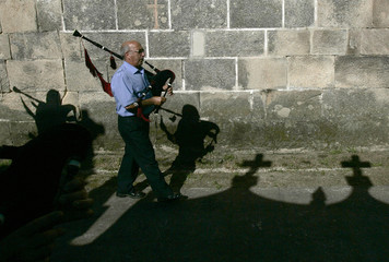 """A man plays the bagpipe during the annual """"Procession of the Shrouds"""" in the village of Ribarteme"""