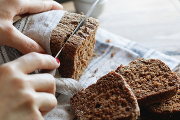 The girl cuts whole-wheat rye bread on a wooden table.