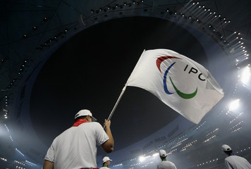A volunteer holds International Paralympic Committee flag during  opening ceremony of Beijing 2008 Paralympic Games at the National Stadium