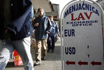 People walk past a board of a small currency exchange office in central Belgrade