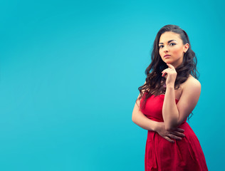 Young  serious girl in a red dress, with makeup on a blue background.