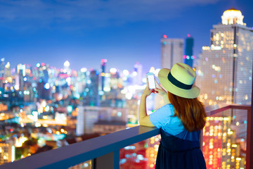 Asian woman is using smart phone with city abstract background.