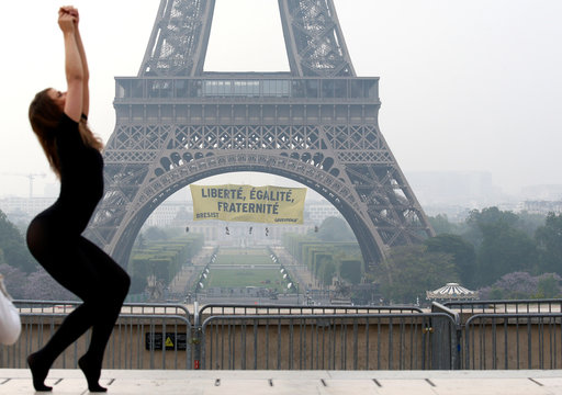 A dancer attends a photo shooting as activists from the environmentalist group Greenpeace unfurl a giant banner on the Eiffel Tower, in Paris