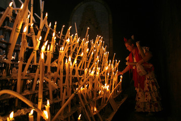 A pilgrim lights candles in the shrine of El Rocio in Almonte, in the province of Huelva