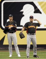 Rogers of the Tigers throws next to Blue Jays Halladay prior to the annual All-Star baseball game in Pittsburgh