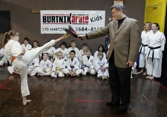 Stephen Harper holds a pad as students of Burtnik Karate demonstrate their kicks in St Catharines