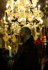 GREEK PRIEST HOLDS A CANDLE AT SUNDAY'S EAST-ORTHODOX MASS IN THECHURCH OF NATIVITY.
