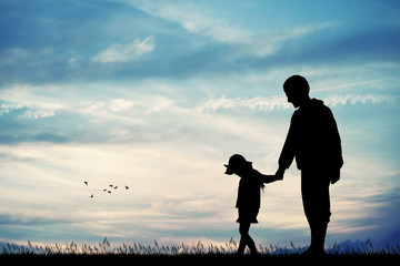 father and child silhouette at sunset