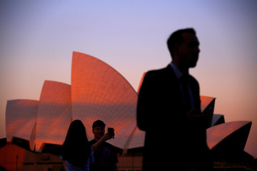 Tourists take photographs of each other in front of the Sydney Opera House at sunset in Sydney