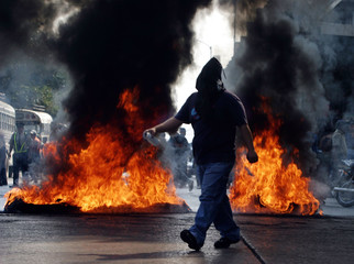 PROTESTER PASSES BURING TIRES DURING DEMONSTRATION BY TEACHERS IN GUATEMALA.