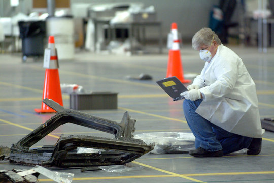 A technician looks at his lap top computer after examining part of a window from the space shuttle C..