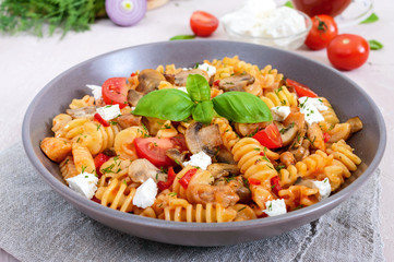 Pasta Radiatori with chicken, mushrooms, cherry tomatoes, feta cheese and tomato sauce on a light background.