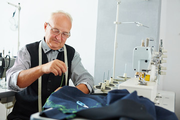 Portrait of pleasing old man working in tailoring studio making clothes at sewing machine and hand stitching cloth