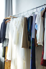 Background image of various ordered garments and dresses hanging on clothes rack in atelier studio