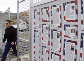 SOLDIER WALKS NEXT TO PHOTOGRAPHS OF VICTIMS OF PENTAGON ATTACK.