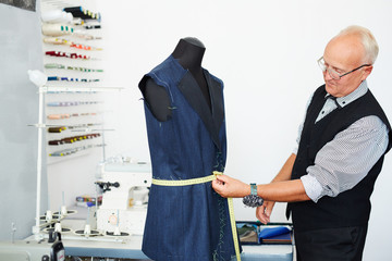 Portrait of grey haired old man measuring waist on mannequin in traditional tailoring studio