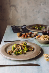 Close up of sauteed mushrooms with broccoli served on concrete plate