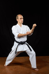 With a black belt, an athlete trains karate blocks