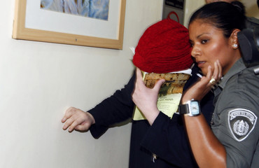 An Ultra-Orthodox Jewish woman, suspected of starving her 3-year-old child, covers her face in court in Jerusalem