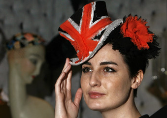 """British model O'Connor poses for photographers while wearing a hat entitled """"Anna P."""" designed by milliner Jones in London"""