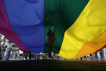 Woman jumps under a rainbow flag during the Gay Pride Parade in Lisbon