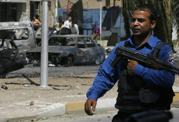A policeman secures the scene of car bomb attacks in Baghdad