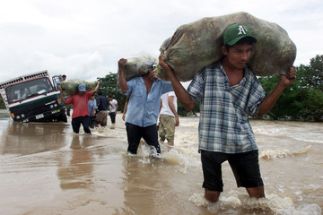 PEOPLE CARRY FOOD DOWN THE FLOODED PAN AMERICAN HIGHWAY.