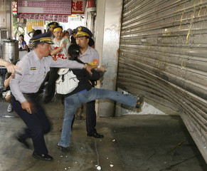 A policeman holds back a woman from kicking the shutters of a bank during a street protest against Taiwan banks linked with Lehman Brothers, in Taipei