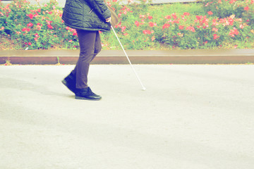 Blind person walking with a stick crossing a pedestrian walkway. Empty copy space for Editor's text.