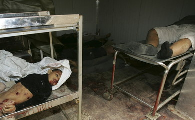 The body of an Iraqi girl lies inside a morgue with other victims after a roadside bomb attack in Am..