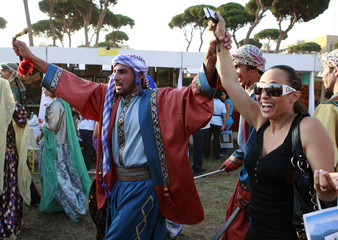 """A performer dances the """"Dabkee"""" with a woman during a festival in a central Beirut park"""