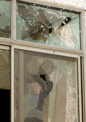 A Palestinian Fatah supporter breaks a window in the Palestinian Council of Ministers building during a protest in Ramallah