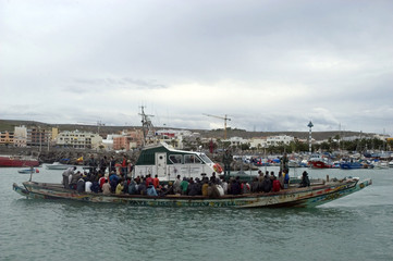 Would-be immigrants arrive at the port of Arguineguin tugged by a civil guard patrol after being intercepted off Spain's Canary Island of Gran Canaria