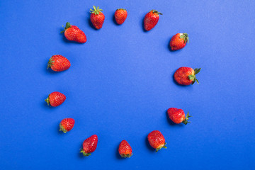 top view of fresh red strawberries in circle isolated on blue, berries background concept