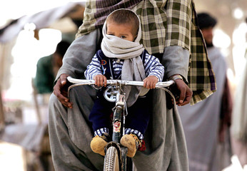A child makes his way through the streets on the front of his fathers bicycle in the southern town of Lashkar Gar