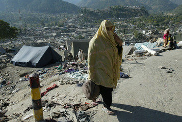 A Pakistani earthquake victim returns after receiving relief aid in Balakot