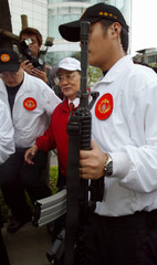 OPPOSITION LEADER LIEN CHAN IS ESCORTED BY BODYGUARDS IN TAIPEI.