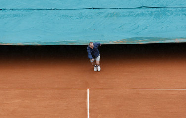 Court worker covers the central court as it rains at Roland Garros stadium in Paris