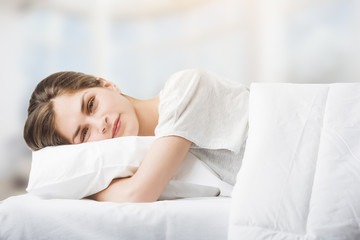a beautiful young woman in bed, feeling happy waking up while hugging her pillow