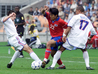 KO JONG-SU OF SOUTH KOREA FIGHTS FOR THE BALL AGAINST ERIC CARRIERE AND STEVE MARLET OF FRANCE ...