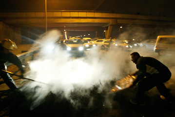 Israeli fire-fighters extinguish burning tyres during a right wing protest at Ayalon highway near ...