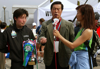 CHINESE TRACK COACH MA JUNREN SPEAKS BESIDE SUN WEIWEI AT HONG KONGMARATHON.