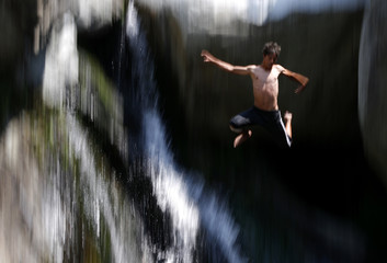 A boy jumps in a waterfall to cool off during a hot day near the town of Karlovo