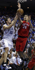 Toronto Raptors guard Carlos Delfino, shoots the ball while defended by Orlando Magic forward Hedo Turkoglu in NBA action from Orlando