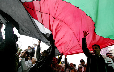 Fatah supporters carry a giant Palestinian flag during a demonstration in Ramallah