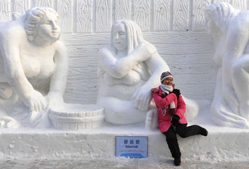A visitor poses for a photograph in front of an ice sculpture in Harbin