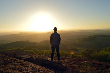 homem observando por do sol nas montanhas