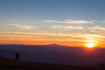 A boy and a girl looking at sunset from the top of a mountain