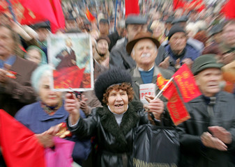 An elderly Ukrainian woman waves red Soviet flags and shouts pro-Communist slogans during a meeting ...