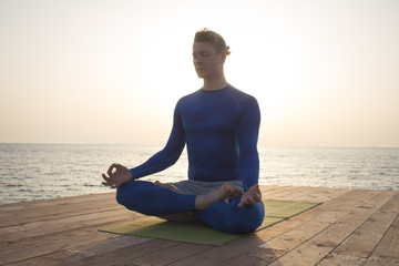 young man meditating in a yoga pose on the wooden pier, morning sea background